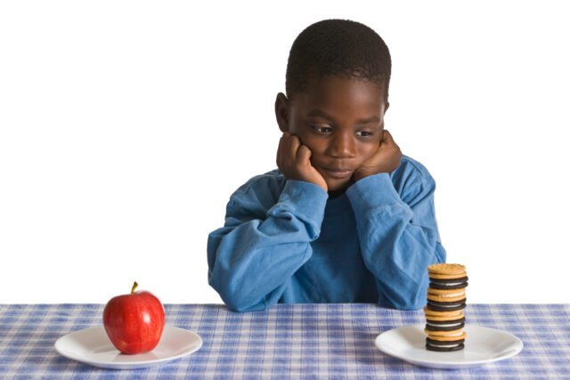 A boy compares cookies and an apple
