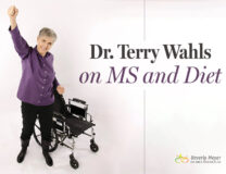 Dr. Terry Wahls stands beside her former wheelchair smiling