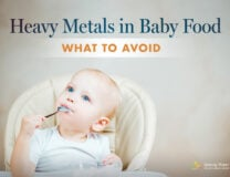 A blue-eyed baby eats from a spoon in the topic of heavy metals in baby food
