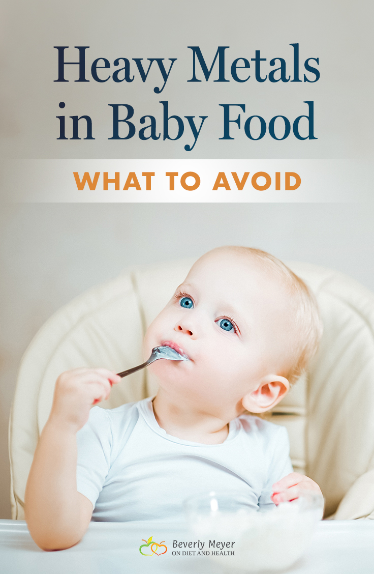 A cute blue-eyed baby is eating from a spoon